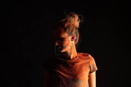 Photo pour Femme avec de la poudre de peinture holi colorée orange sur la peau et des vêtements isolés sur noir - image libre de droit