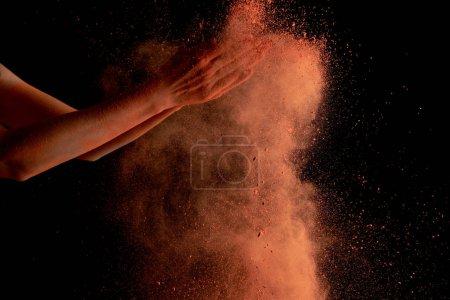 Photo pour Crocheté des mains de la femme avec une peinture holi orange éclatée sur fond noir - image libre de droit