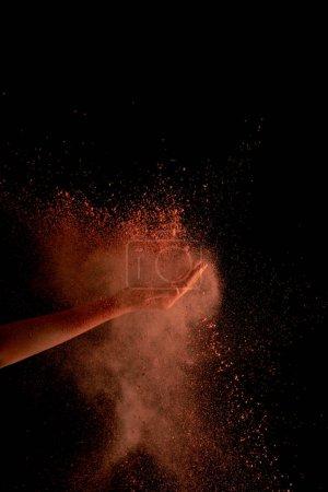 Photo pour Crocheté de la main d'une femme avec une peinture holi orange éclatée sur fond noir - image libre de droit