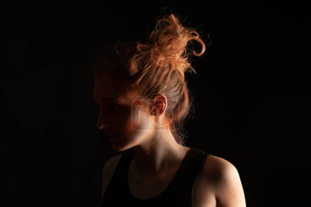 Photo pour Femme avec de la peinture holi orange en poudre sur le visage isolée sur noir - image libre de droit