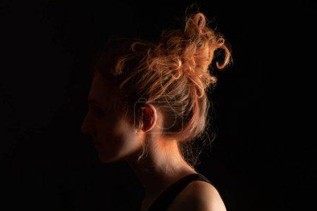Photo pour Profil de la femme avec de la peinture holi orange en poudre sur le visage isolée sur noir - image libre de droit