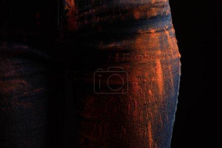 Photo pour Vue recadrée de la femme avec de la poudre de peinture holi colorée orange sur jeans isolés sur noir - image libre de droit