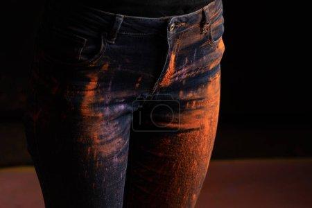 Photo pour Vue recadrée de la femme avec de la poudre de peinture holi colorée orange sur jeans sur fond noir - image libre de droit