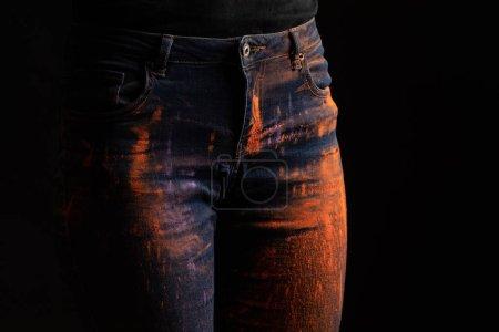 Photo pour Crocheté d'une femme avec de la peinture orange holi en poudre sur des jeans isolés en noir - image libre de droit