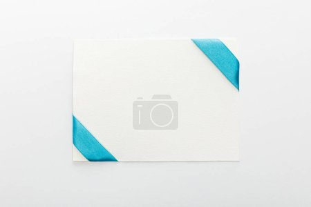 Photo for Top view of blank card with blue decorative satin ribbon on white background - Royalty Free Image