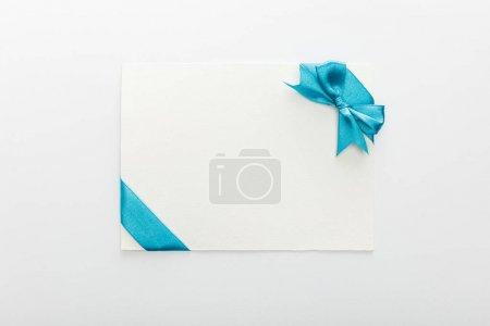 Photo pour Vue du dessus de la carte blanche avec ruban de satin décoratif bleu et arc sur fond blanc - image libre de droit