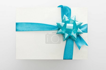 top view of blank card with blue decorative satin ribbon and bow on white background