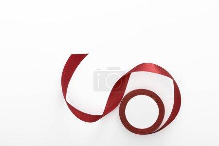 Photo pour Vue du dessus du ruban décoratif bordeaux satiné courbé isolé sur blanc - image libre de droit