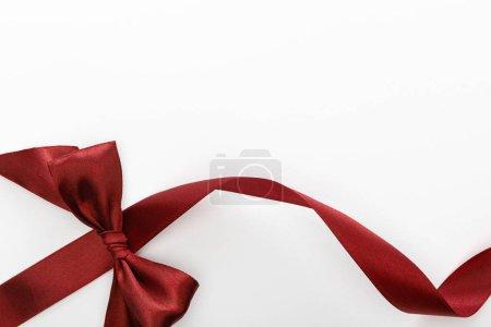 Foto de Vista superior de la cinta curvada decorativa burdeos satinado con arco aislado en blanco - Imagen libre de derechos