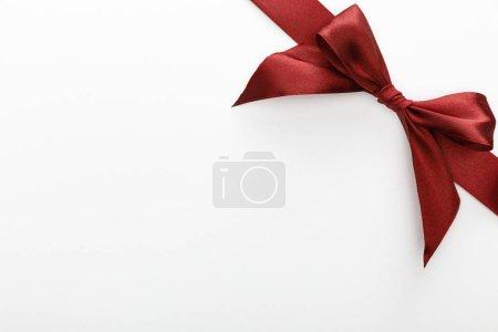 Photo pour Vue du dessus du ruban décoratif bordeaux satiné avec noeud isolé sur blanc - image libre de droit