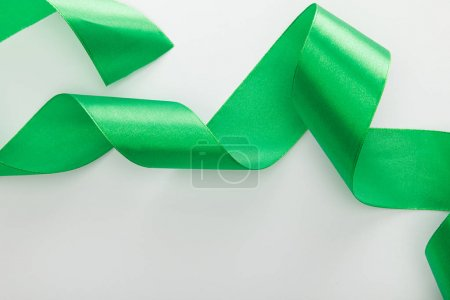 top view of satin green decorative curved ribbon isolated on white