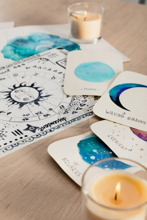 Photo for Selective focus of watercolor drawings with moon phases on cards and zodiac signs on wooden table with candles - Royalty Free Image