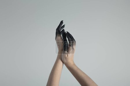 Photo pour Vue croûtée de mains de sorcière peintes en noir isolées sur gris - image libre de droit