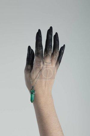 Photo pour Vue croûtée d'une main de sorcière en peinture noire tenant du cristal isolé sur gris - image libre de droit