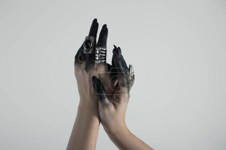 Foto de Vista cruzada de la mano de bruja en pintura negra con anillos de joyería aislados en gris. - Imagen libre de derechos