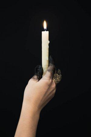 Photo pour Vue agrandie d'une sorcière avec de la peinture noire en main et un anneau de bijoux tenant une bougie isolée sur noir - image libre de droit