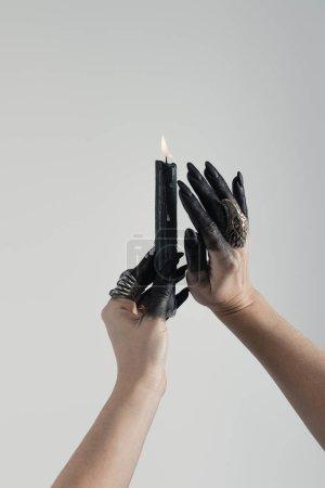 Foto de Vista cruzada de las manos de bruja pintadas en negro con anillos de joyería y velas aisladas en gris. - Imagen libre de derechos