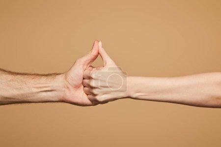 Photo pour Vue recadrée de l'homme et de la femme tenant les mains isolées sur beige - image libre de droit