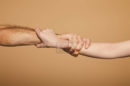 cropped view of man and woman holding hands isolated on beige