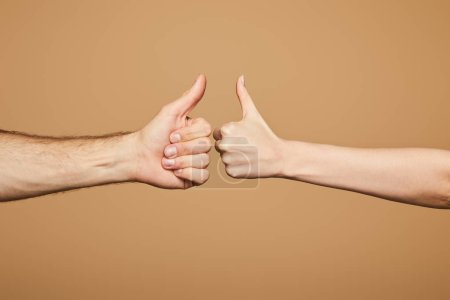 cropped view of man and woman showing thumbs up isolated on beige
