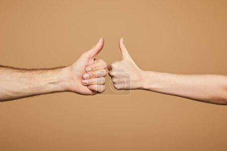 Foto de Vista rota del hombre y la mujer mostrando pulgares aislados sobre la colza. - Imagen libre de derechos