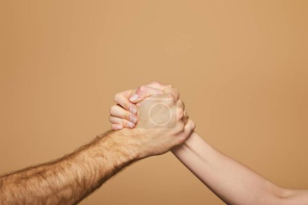 cropped view of man and woman arm wrestling isolated on beige
