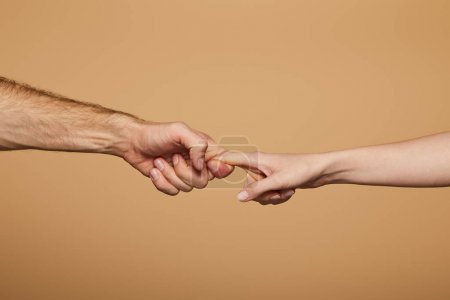 cropped view of man and woman holding fingers isolated on beige