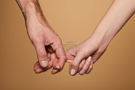 Photo for Cropped view of man and woman holding fingers isolated on beige - Royalty Free Image
