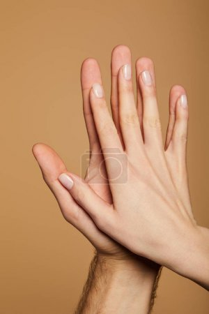 Photo pour Vue recadrée de l'homme et la femme donnant haute cinq isolé sur beige - image libre de droit