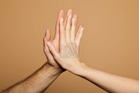cropped view of man and woman giving high five isolated on beige