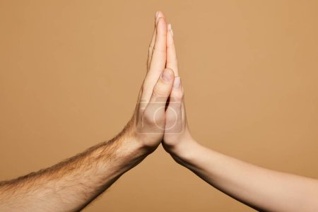 Photo for Cropped view of man and woman giving high five isolated on beige - Royalty Free Image