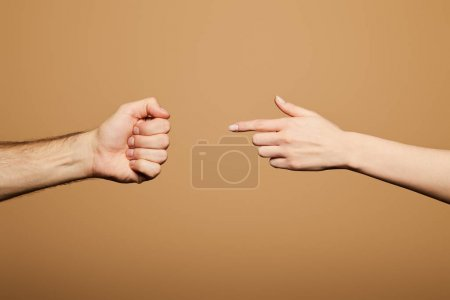 Photo for Cropped view of woman pointing with finger at man fist isolated on beige - Royalty Free Image