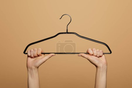 Photo for Cropped view of woman holding empty hanger isolated on beige - Royalty Free Image