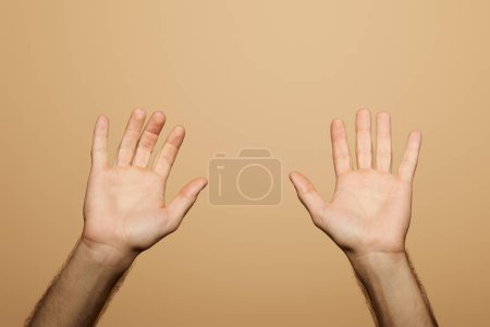 Photo for Cropped view of man showing palms isolated on beige - Royalty Free Image