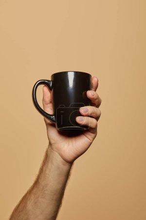 Photo pour Vue recadrée de l'homme tenant une tasse noire isolée sur beige - image libre de droit
