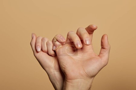 cropped view of man and woman holding little fingers isolated on beige