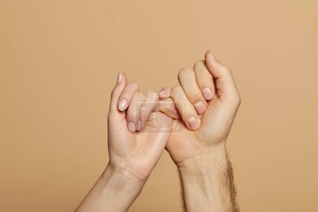 Photo for Cropped view of man and woman holding little fingers isolated on beige - Royalty Free Image