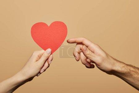 Photo pour Vue recadrée de la femme tenant le cœur rouge et l'homme l'atteignant isolé sur beige - image libre de droit
