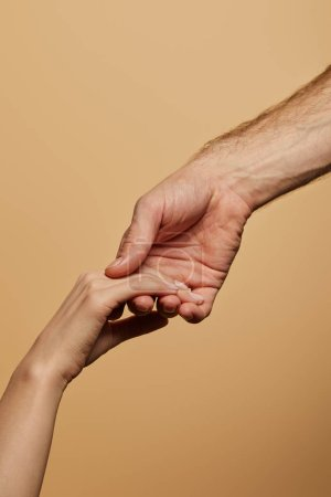 cropped view of man holding woman hand isolated on beige