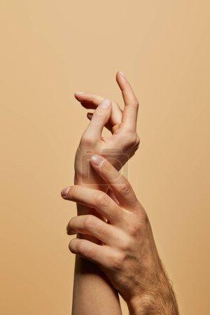 Photo pour Vue recadrée de l'homme touchant la main de la femme isolé sur beige - image libre de droit