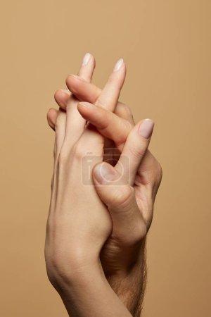 vista parcial del hombre y la mujer tomados de la mano aislados en beige