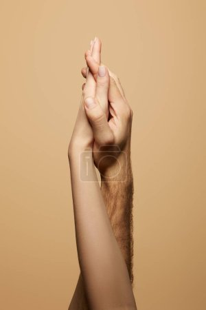 partial view of man and woman holding hands isolated on beige