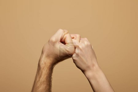 Photo pour Vue partielle de l'homme et de la femme tenant les mains et les doigts isolés sur beige - image libre de droit
