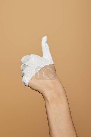 vista recortada de la mujer con la mano pintada de blanco que muestra el pulgar hacia arriba aislado en beige