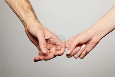 cropped view of man and woman holding fingers isolated on white