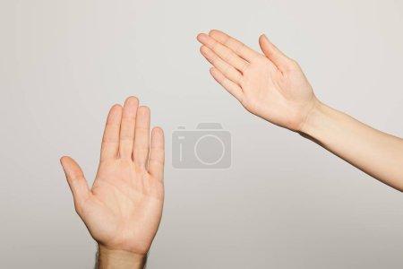 Photo pour Vue recadrée de l'homme et de la femme montrant les paumes isolées sur gris - image libre de droit