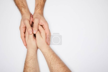 top view of two men holding hands isolated on white