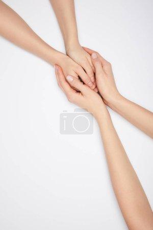 Draufsicht von zwei Frauen, die Hände isoliert auf Weiß halten