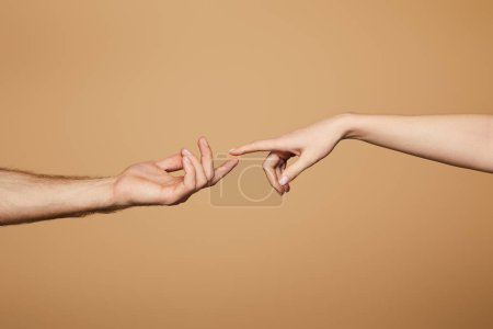 Photo for Cropped view of man and woman reaching each other with fingers isolated on beige - Royalty Free Image