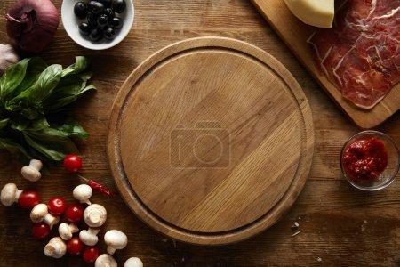 Photo pour Vue aérienne des ingrédients de la pizza autour de la planche à découper sur fond de bois - image libre de droit